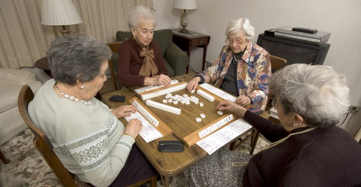 group of happy senior women playing mah-jong with friends
